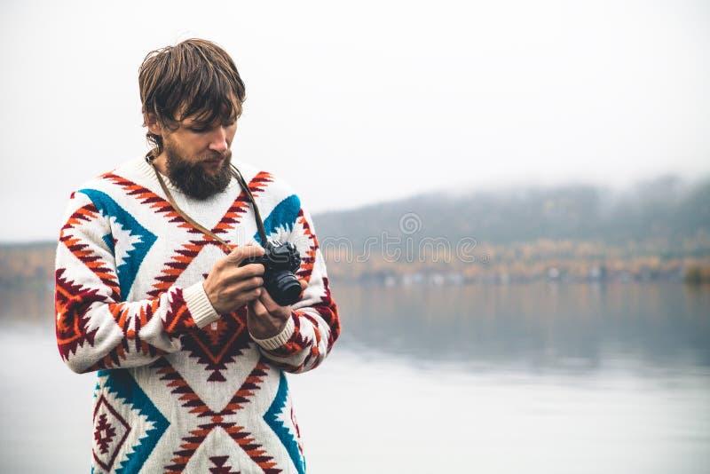 Jeune homme barbu avec le rétro mode de vie de voyage de mode d'appareil-photo de photo photo stock