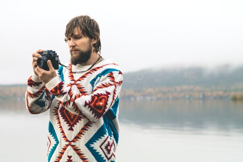 Jeune homme barbu avec le rétro mode de vie de voyage de mode d'appareil-photo de photo image libre de droits