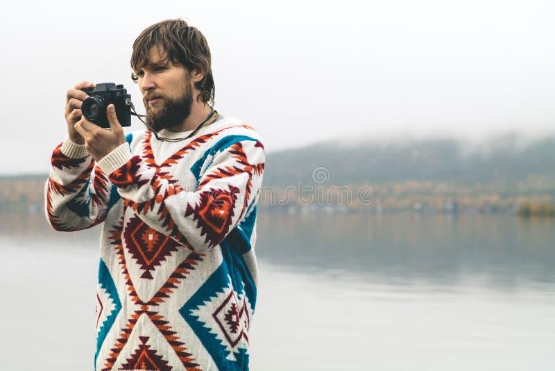 Jeune homme barbu avec le rétro mode de vie de voyage de mode d'appareil-photo de photo photos stock