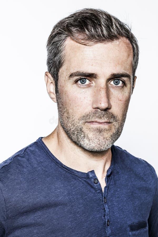 Jeune homme barbu beau avec des yeux bleus et des taches de rousseur semblant futés photos stock