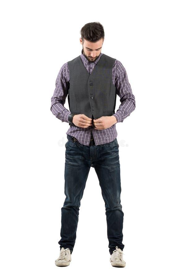 Jeune homme barbu boutonnant le gilet regardant vers le bas photo stock