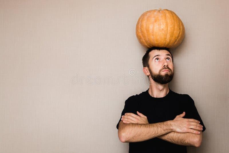 Jeune homme barbu dans le T-shirt noir tenant le petit potiron au-dessus de sa tête images stock
