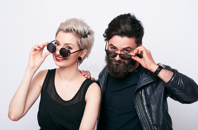 Jeune homme barbu et femme blonde à la mode regardant l'appareil-photo photographie stock