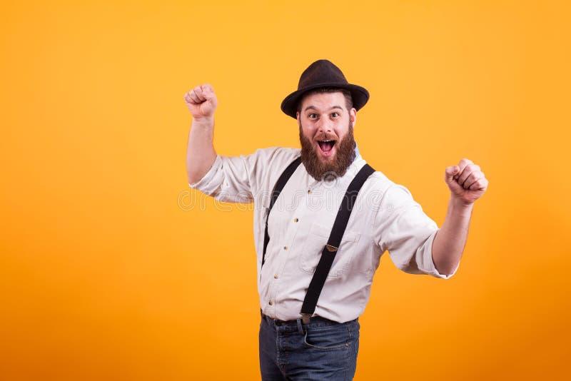 Jeune homme barbu gai utilisant un chapeau et souriant regardant la caméra au-dessus du fond jaune images libres de droits