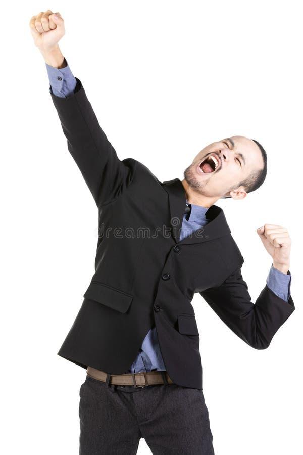Jeune homme barbu heureux dans le tenue de soirée maintenant des bras augmentés et exprimant la positivité images stock