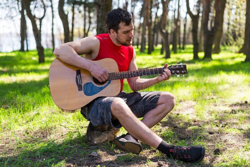 Jeune homme barbu jouant une guitare acoustique, dehors photos libres de droits