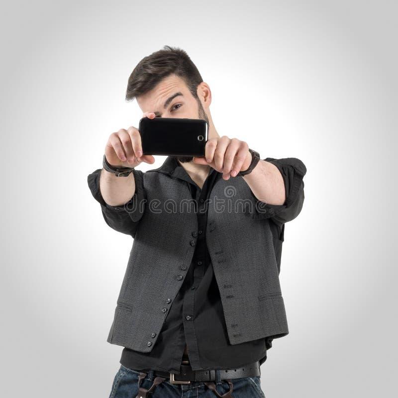 Jeune homme barbu prenant la photo avec son appareil-photo futé de téléphone photographie stock