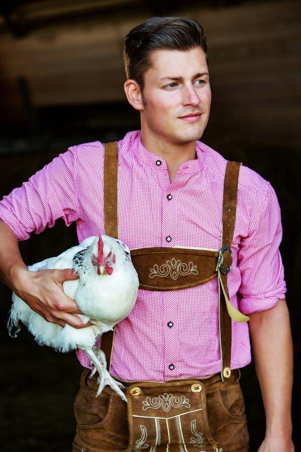 Jeune homme bavarois tenant un poulet blanc photos stock