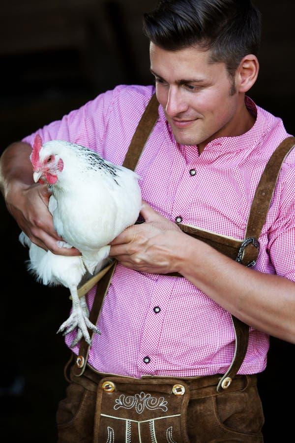 Jeune homme bavarois tenant un poulet blanc photo libre de droits