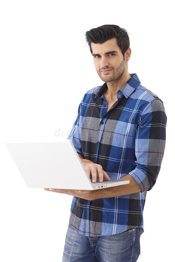Jeune homme beau à l'aide de l'ordinateur portatif image libre de droits