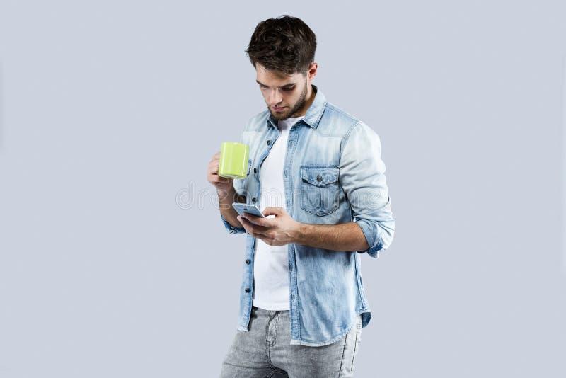 Jeune homme beau à l'aide de son téléphone portable au-dessus de fond gris images stock