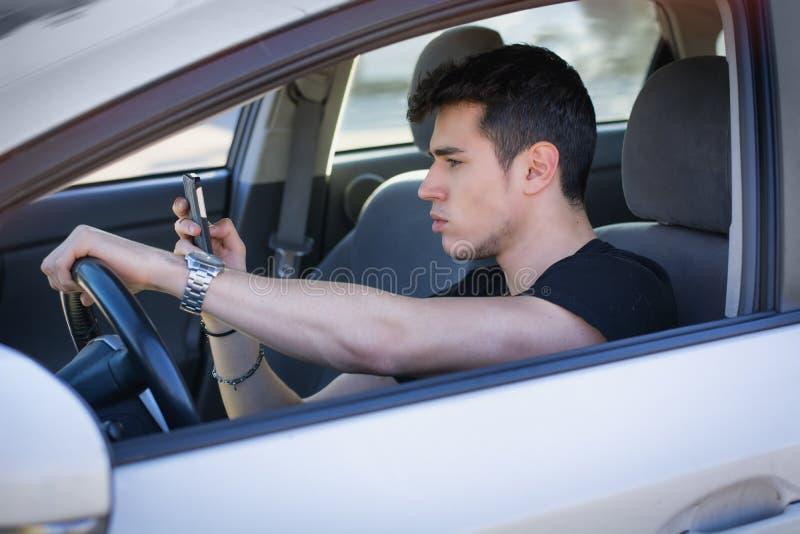 Jeune homme beau à l'aide de son téléphone portable conduisant a photographie stock libre de droits