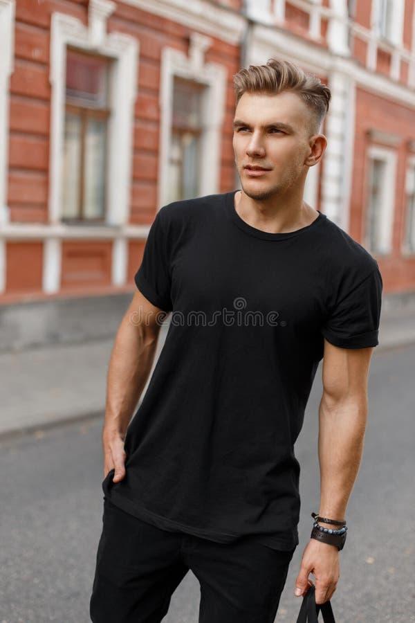 Jeune homme beau élégant avec la coiffure dans la chemise noire image libre de droits