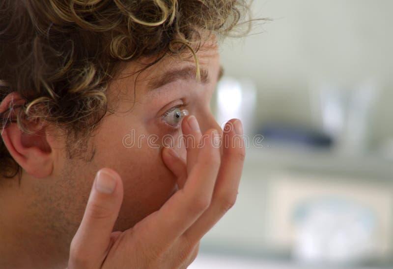 Jeune homme beau appliquant le verre de contact photographie stock libre de droits