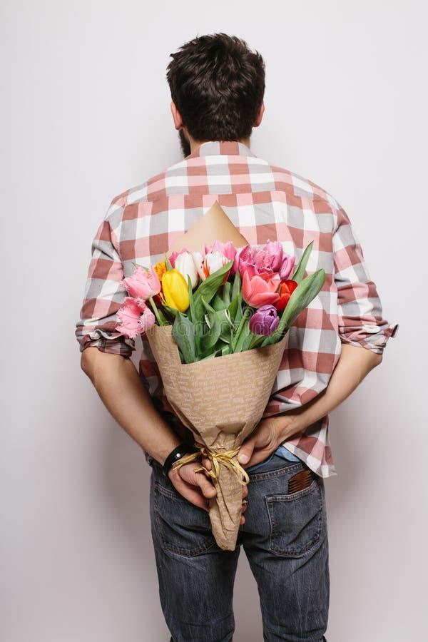 Jeune homme beau arrière avec la barbe et le bouquet gentil des fleurs photographie stock libre de droits
