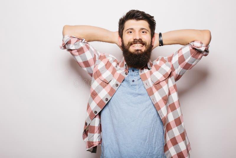 Jeune homme beau avec la barbe tenant des mains derrière la tête et le sourire photos libres de droits
