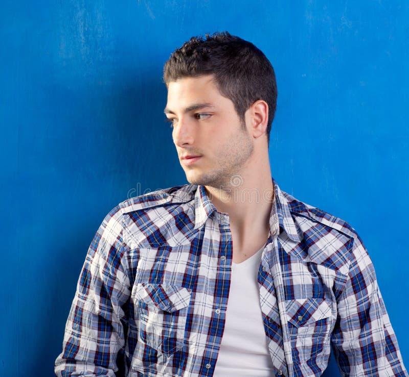 Jeune homme beau avec la chemise de plaid sur le bleu photos stock