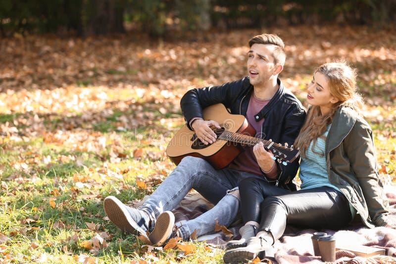 Jeune homme beau avec la guitare et son repos aimé en parc d'automne images stock