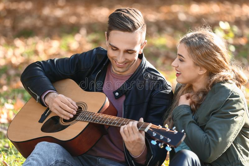 Jeune homme beau avec la guitare et son repos aimé en parc d'automne image libre de droits