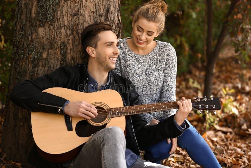 Jeune homme beau avec la guitare et son repos aimé en parc d'automne images libres de droits