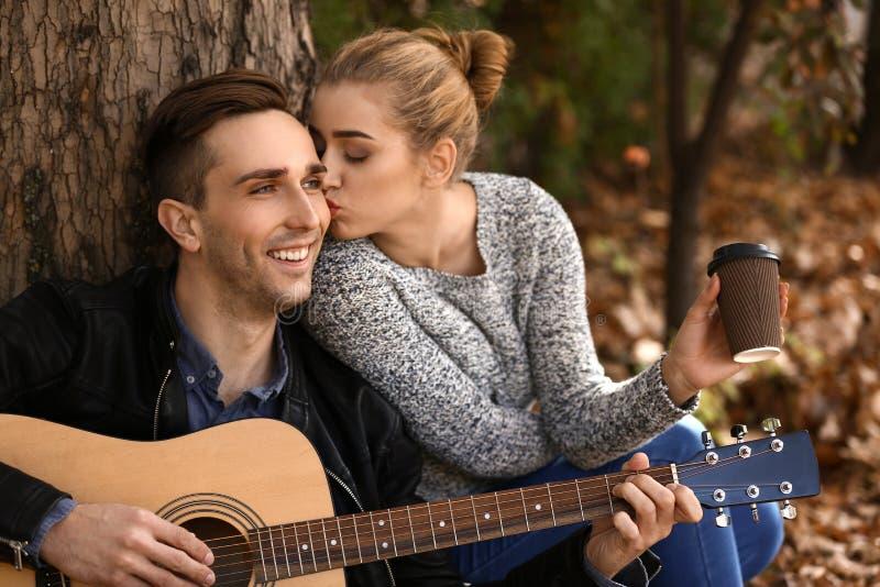 Jeune homme beau avec la guitare et son repos aimé en parc d'automne image stock