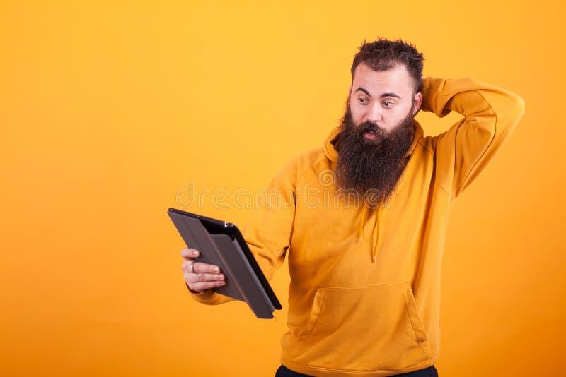 Jeune homme beau avec la longue barbe regardant confuse le comprimé au-dessus du fond jaune images libres de droits