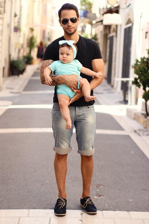 Jeune homme beau avec le bébé marchant à l'intérieur d'une rue Plein chiffre tir image libre de droits
