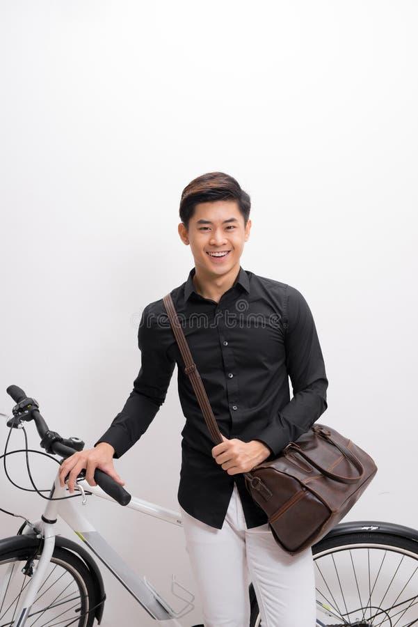 Jeune homme beau avec le sac d'épaule et l'isolat debout de bicyclette photographie stock