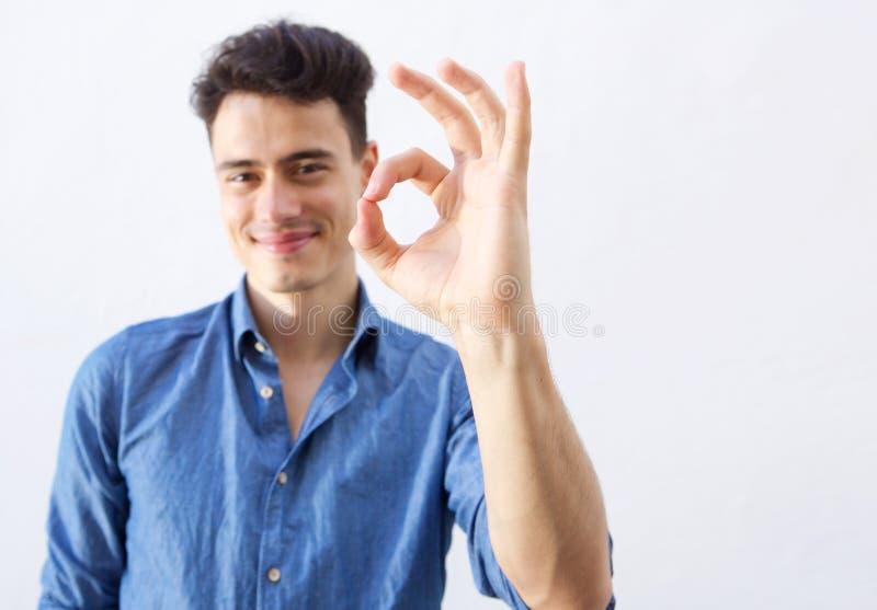 Jeune homme beau avec le signe correct de main image stock