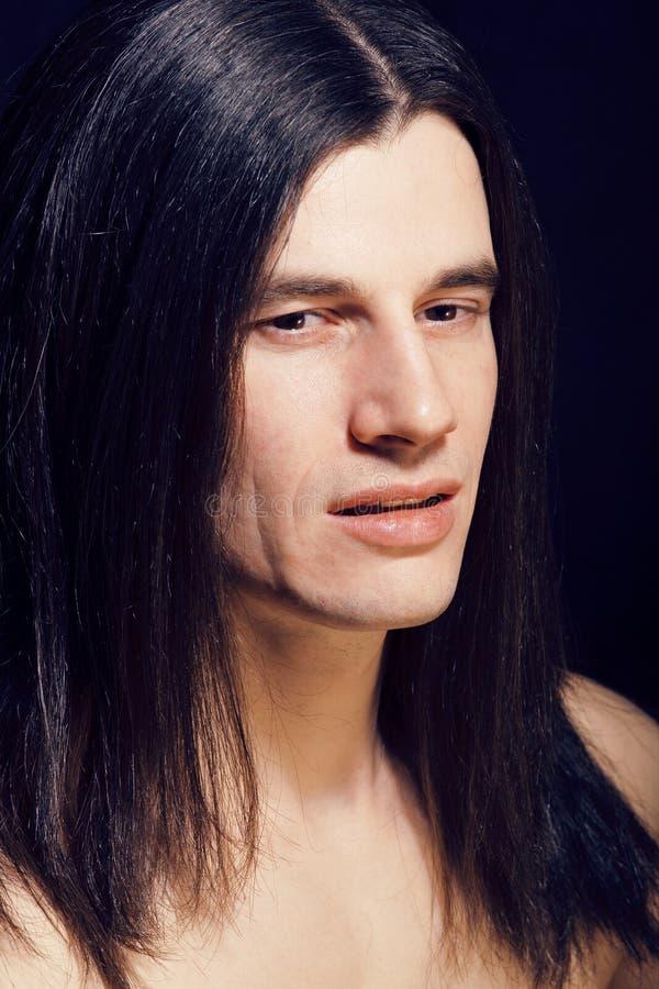 Jeune homme beau avec le torse nu de longs cheveux sur le backgroun noir photos stock