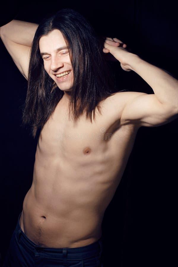 Jeune homme beau avec le torse nu de longs cheveux sur le fond noir souriant, concept de personnes de mode de vie image stock