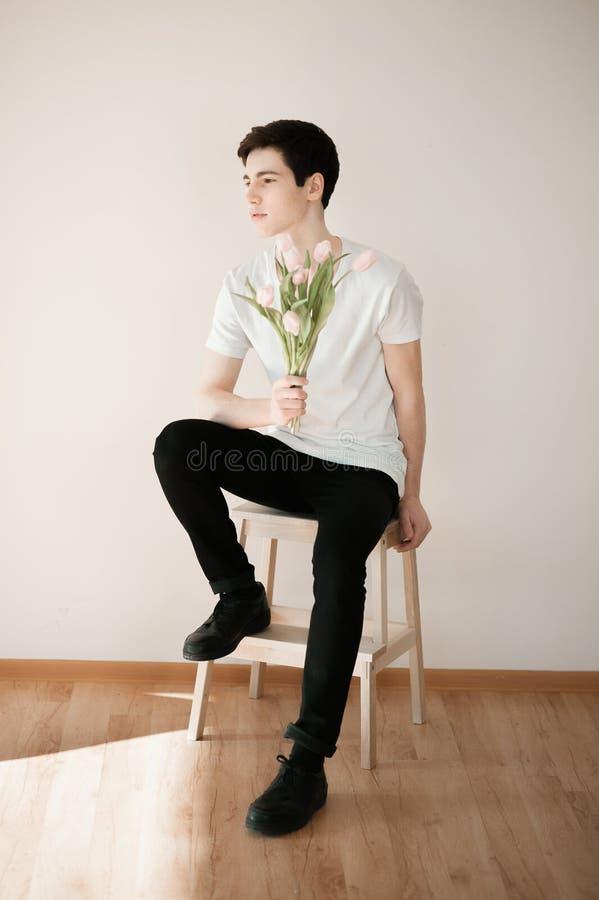 Jeune homme beau avec les tulipes roses photo libre de droits