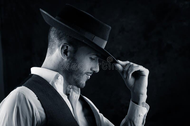 Jeune homme beau avec un fond de noir de chapeau image libre de droits