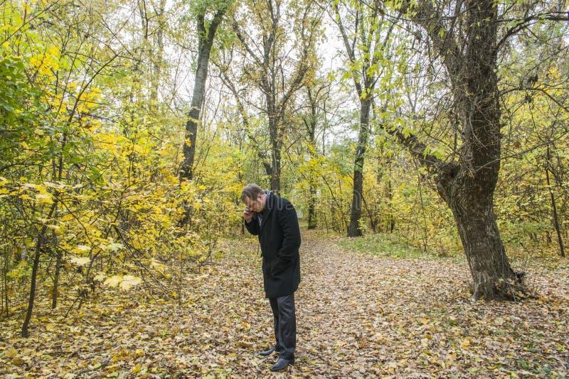 Jeune homme beau avec un smartphone sur la rue parlant en parc image stock
