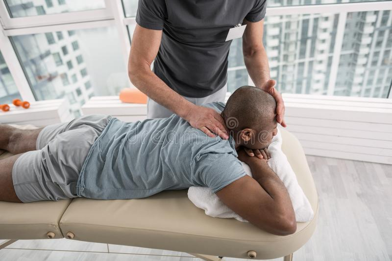 Jeune homme beau ayant une thérapie de massage photos stock