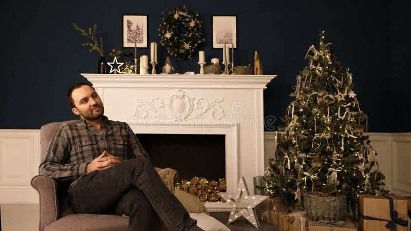 Jeune homme beau barbu de hippie dans roomthinking de Noël des idées de cadeau rêverie photographie stock