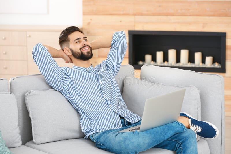 Jeune homme beau décontracté avec l'ordinateur portable sur le sofa Faire la pause pendant le travail images stock