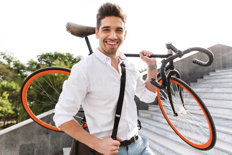 Jeune homme beau d'affaires marchant dehors avec la bicyclette images libres de droits