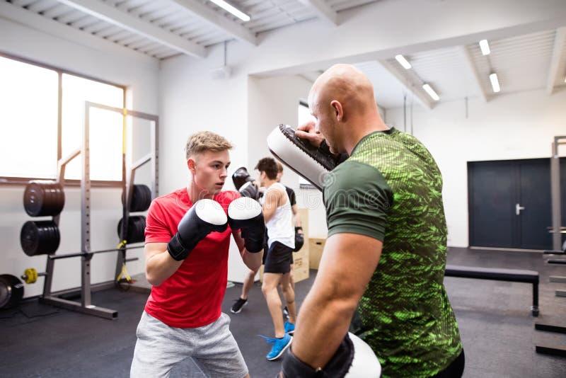 Jeune homme beau d'ajustement dans la boxe de gymnase avec son entraîneur images stock