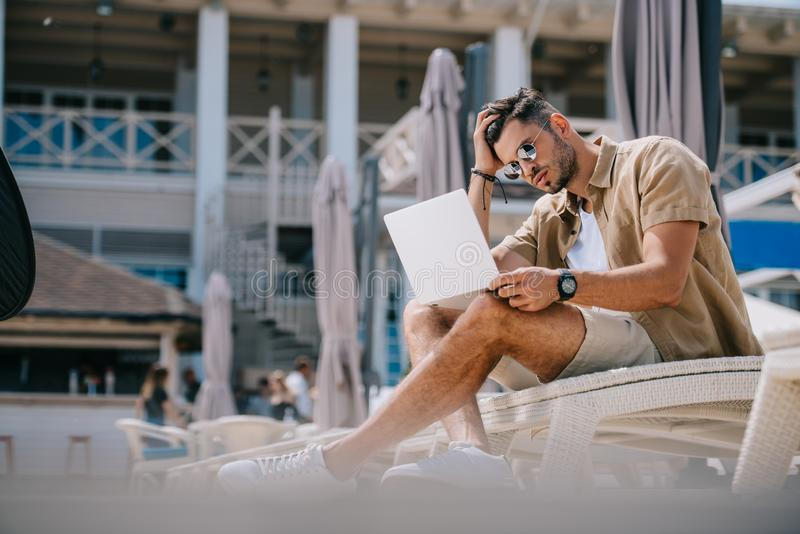 jeune homme beau dans des lunettes de soleil utilisant l'ordinateur portable tout en se reposant sur le cabriolet image libre de droits