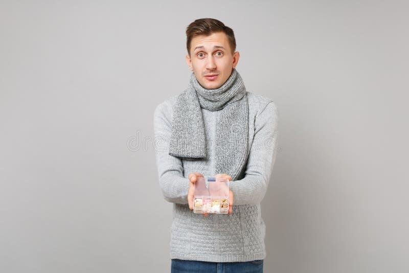 Jeune homme beau dans le chandail gris, écharpe tenant la boîte quotidienne de pilule sur le fond gris, portrait de studio Sain images libres de droits