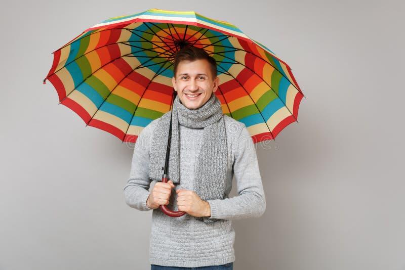 Jeune homme beau dans le chandail gris, écharpe tenant le parapluie coloré sur le fond gris dans le studio Sain image stock