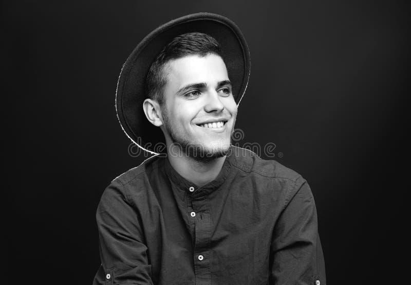Jeune homme beau dans le chapeau élégant sur le fond foncé, noir et blanc image stock