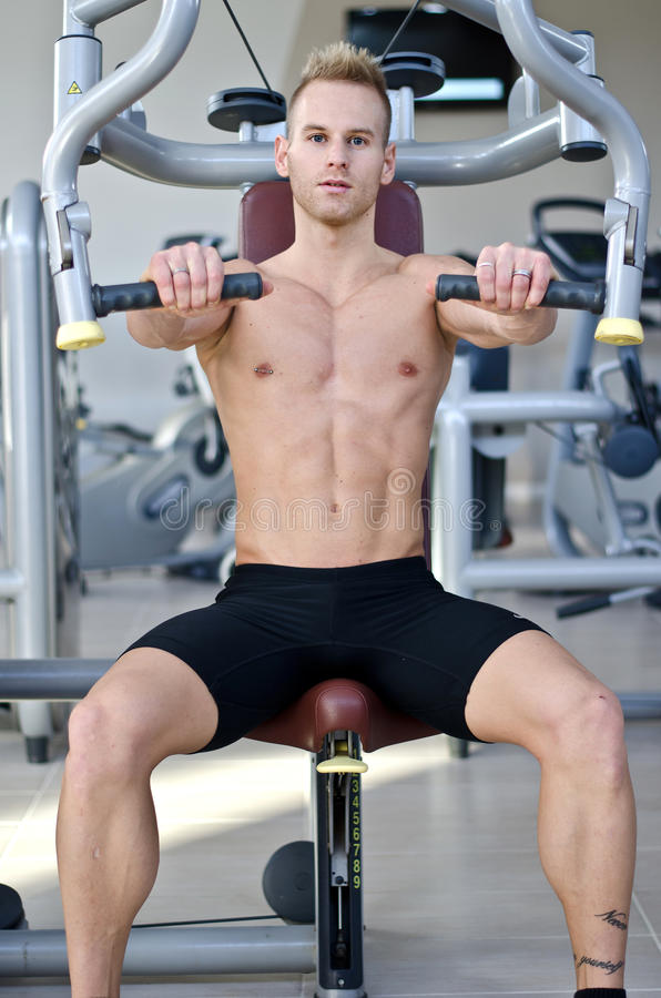 Jeune homme beau dans le gymnase exerçant Pecs sur la machine photographie stock libre de droits