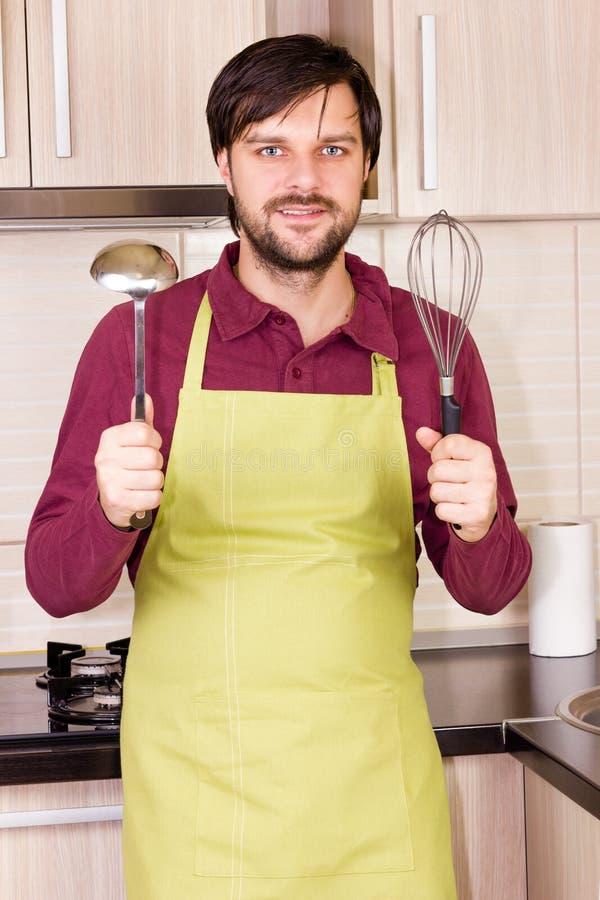 Jeune homme beau dans le tablier de port de cuisine tenant un batteur photographie stock libre de droits