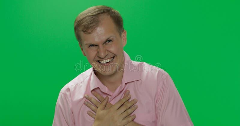 Jeune homme beau dans rire rose de chemise Plan rapproch? photos libres de droits