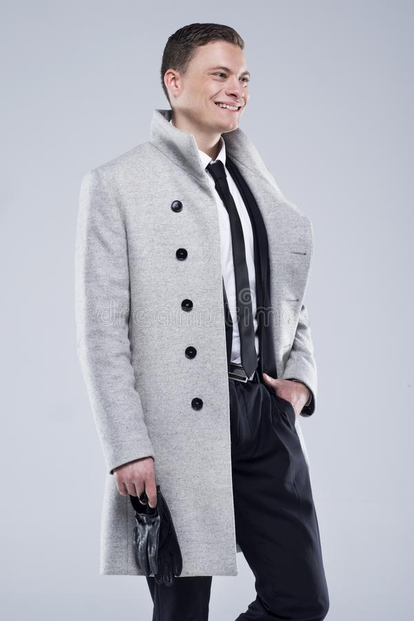 Jeune homme beau dans un manteau gris et un costume noir photographie stock libre de droits