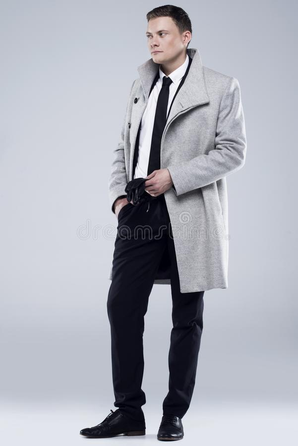Jeune homme beau dans un manteau gris et un costume noir photos libres de droits