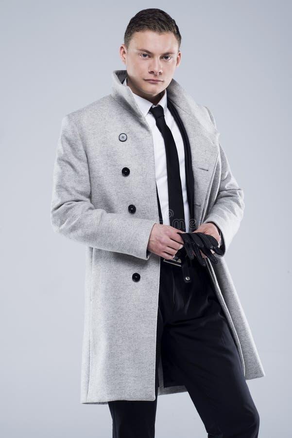 Jeune homme beau dans un manteau gris et un costume noir images stock
