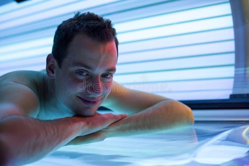 Jeune homme beau dans un solarium moderne images libres de droits